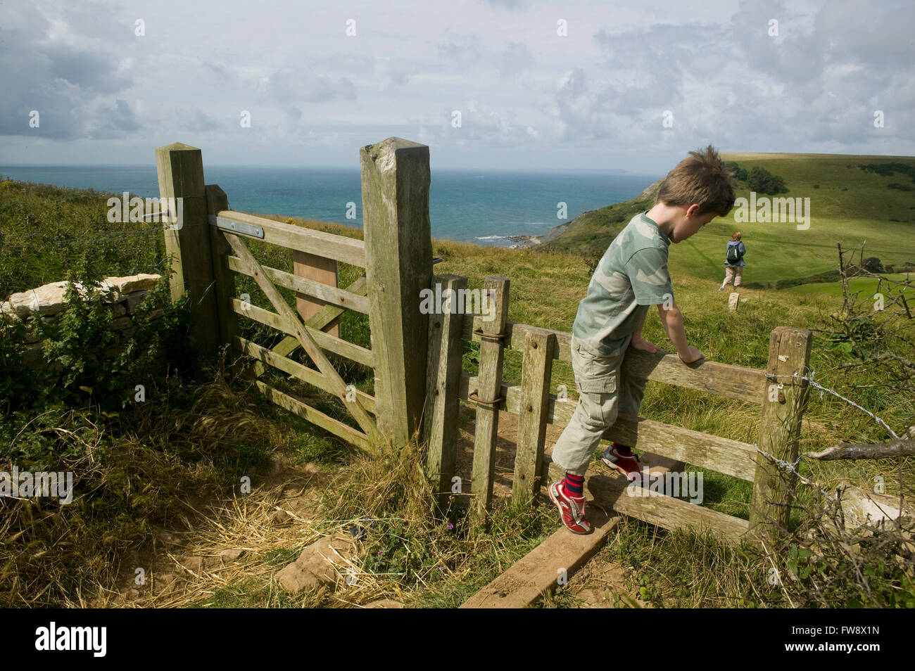 A young boy lags behind his family as they go on a walk along the cliff path in Dorset, UK. Climbing ove r a stile - Stock Image