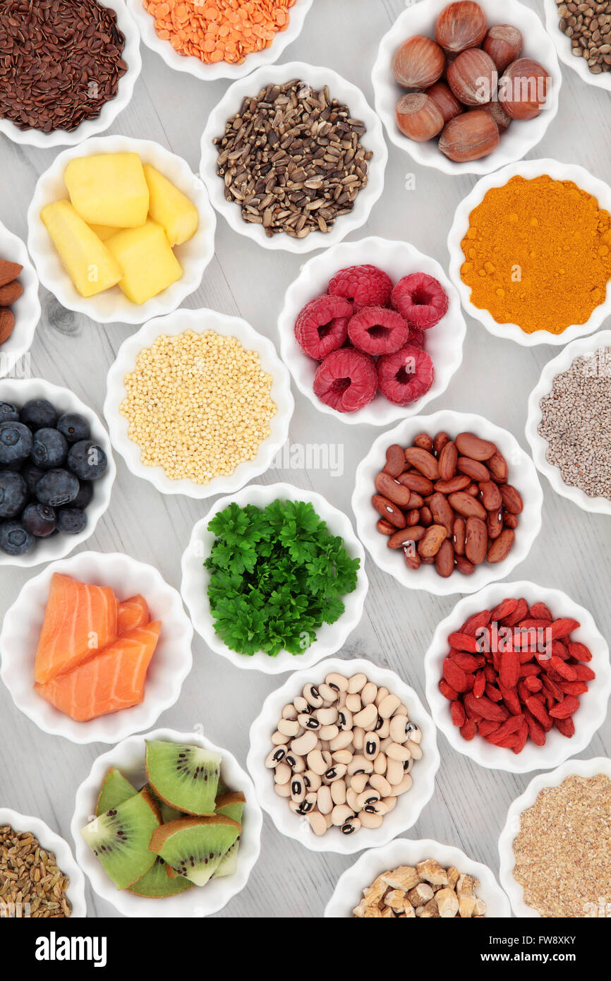 Healthy super food selection in porcelain crinkle bowls over distressed wooden background. High in vitamins and - Stock Image