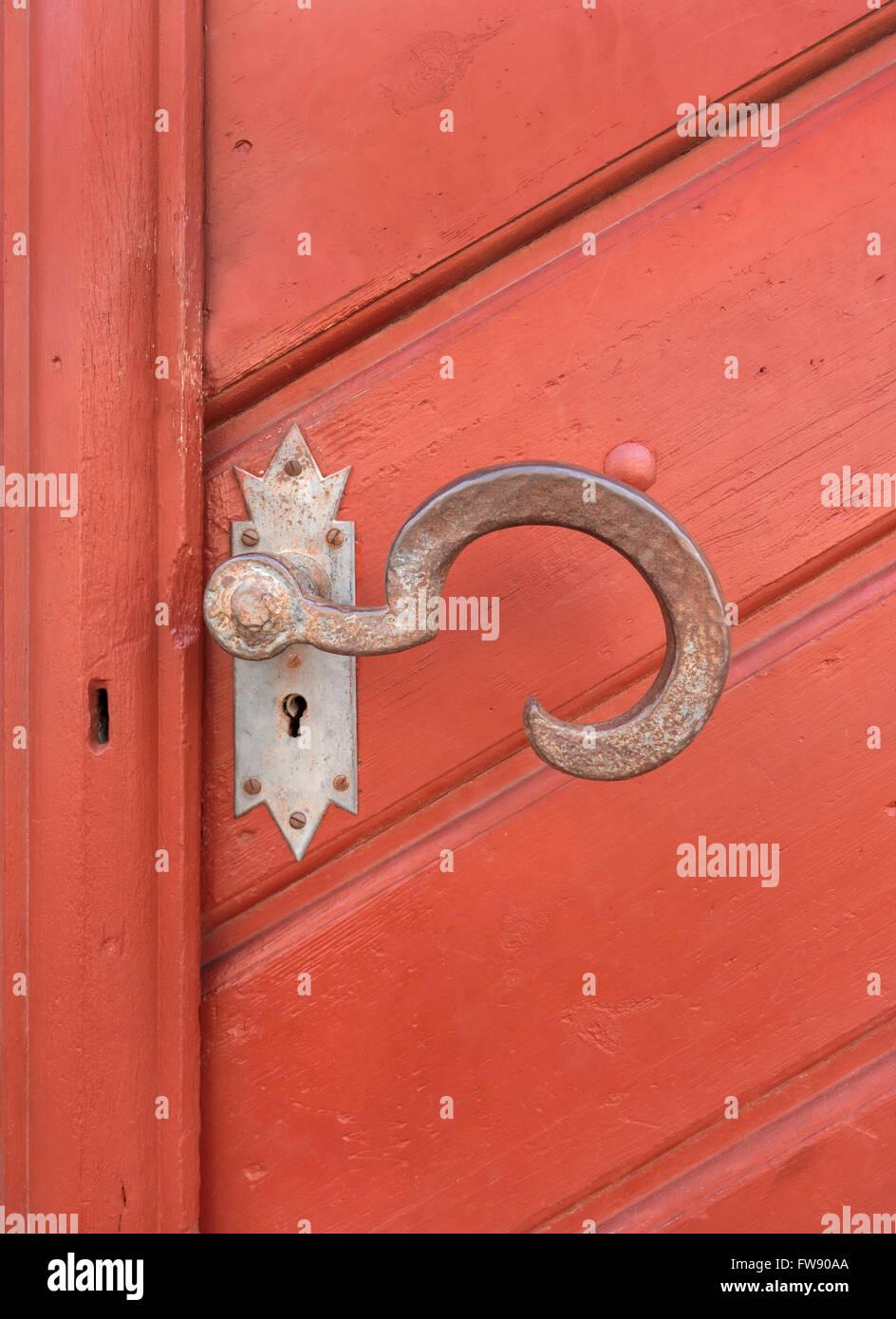 Old, big, artistically curved door handle of rusted metal on a reddish brown wooden door - Stock Image