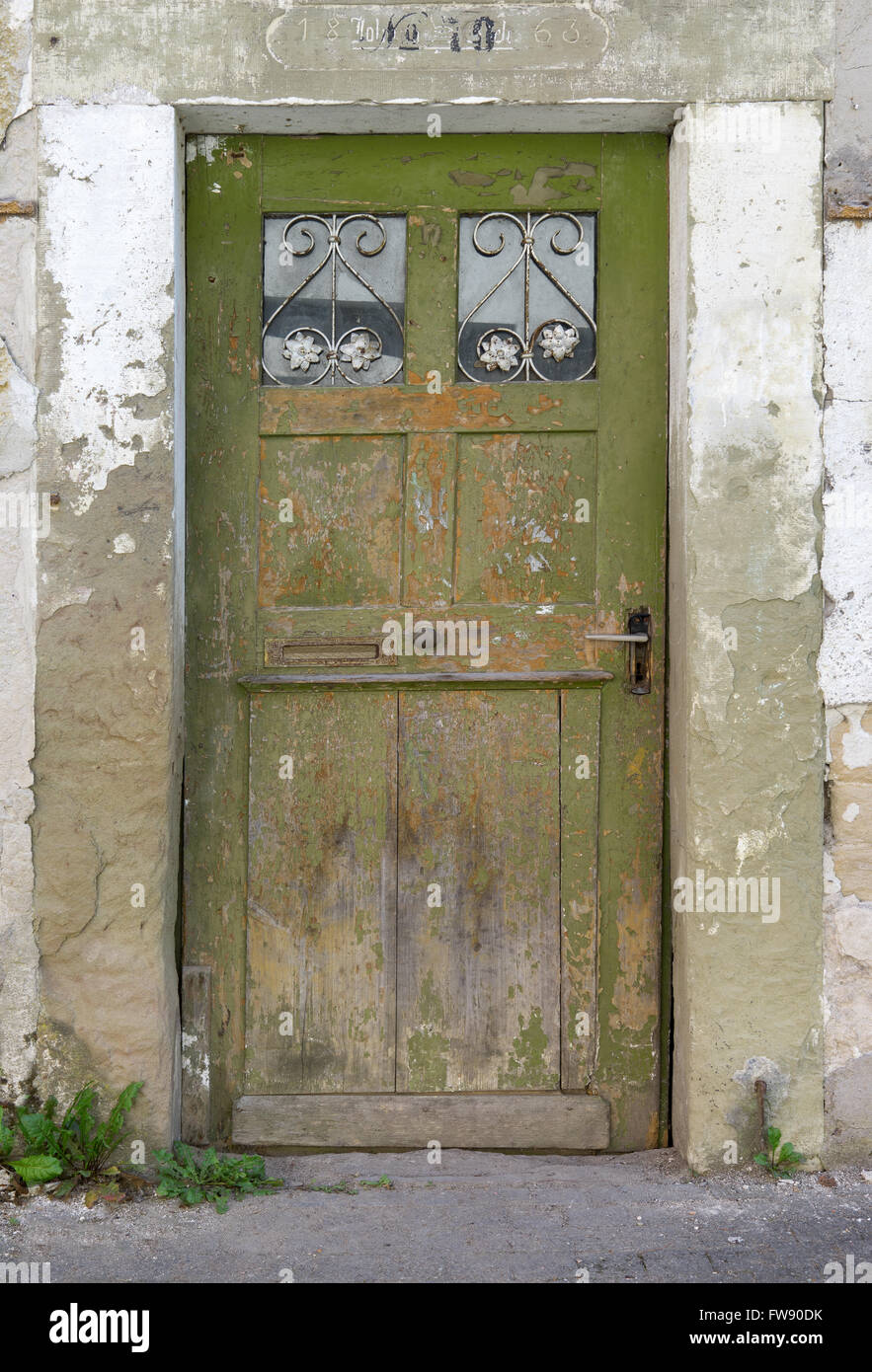 Old, green, weathered wooden door with two small barred glass panes ...