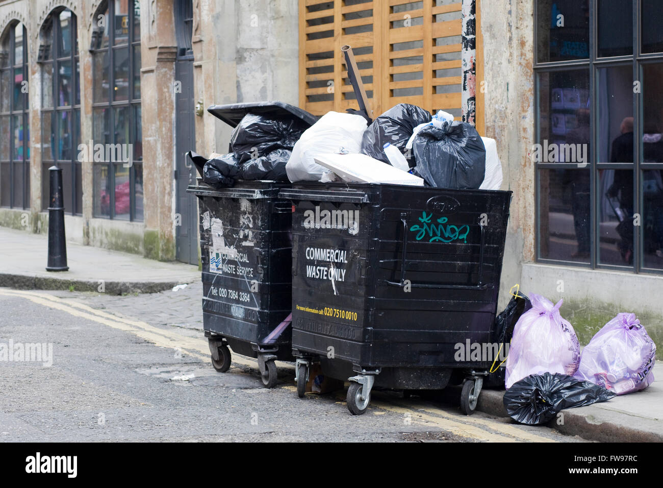 Industrial bins full of plastic bags and refuge - Stock Image