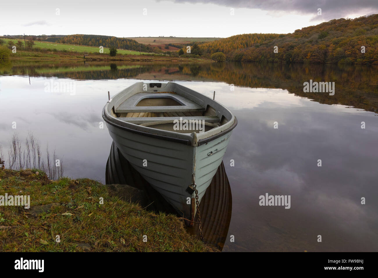 A rowing boat chained to the bank on a still morning on Tunstall reservoir near Wolsingham in Weardale, County Durham. - Stock Image