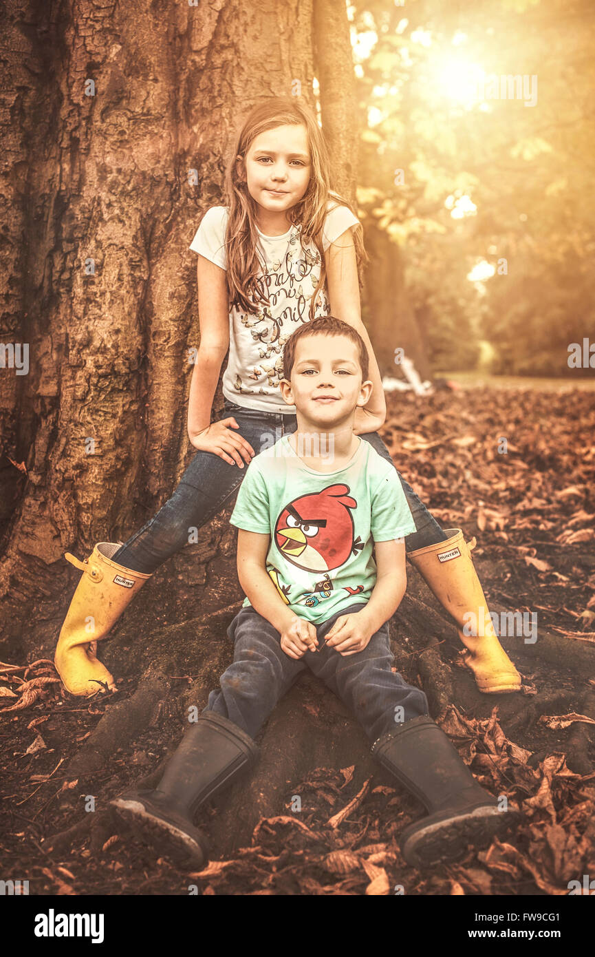 two children sitting by tree - Stock Image