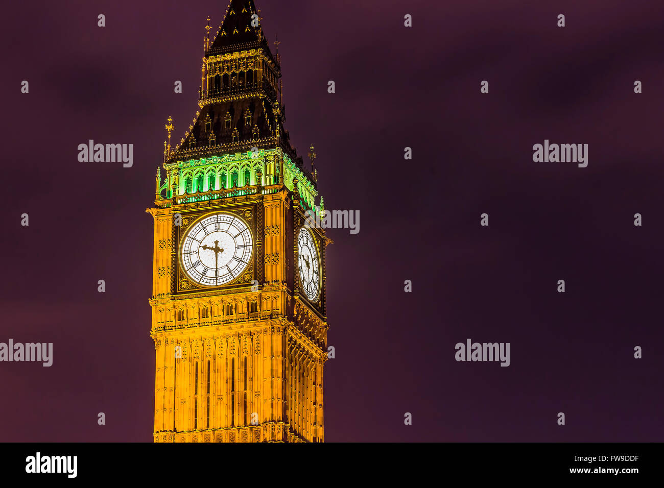 Elizabeth Tower's clock and Big Ben by night on a purple sky. - Stock Image