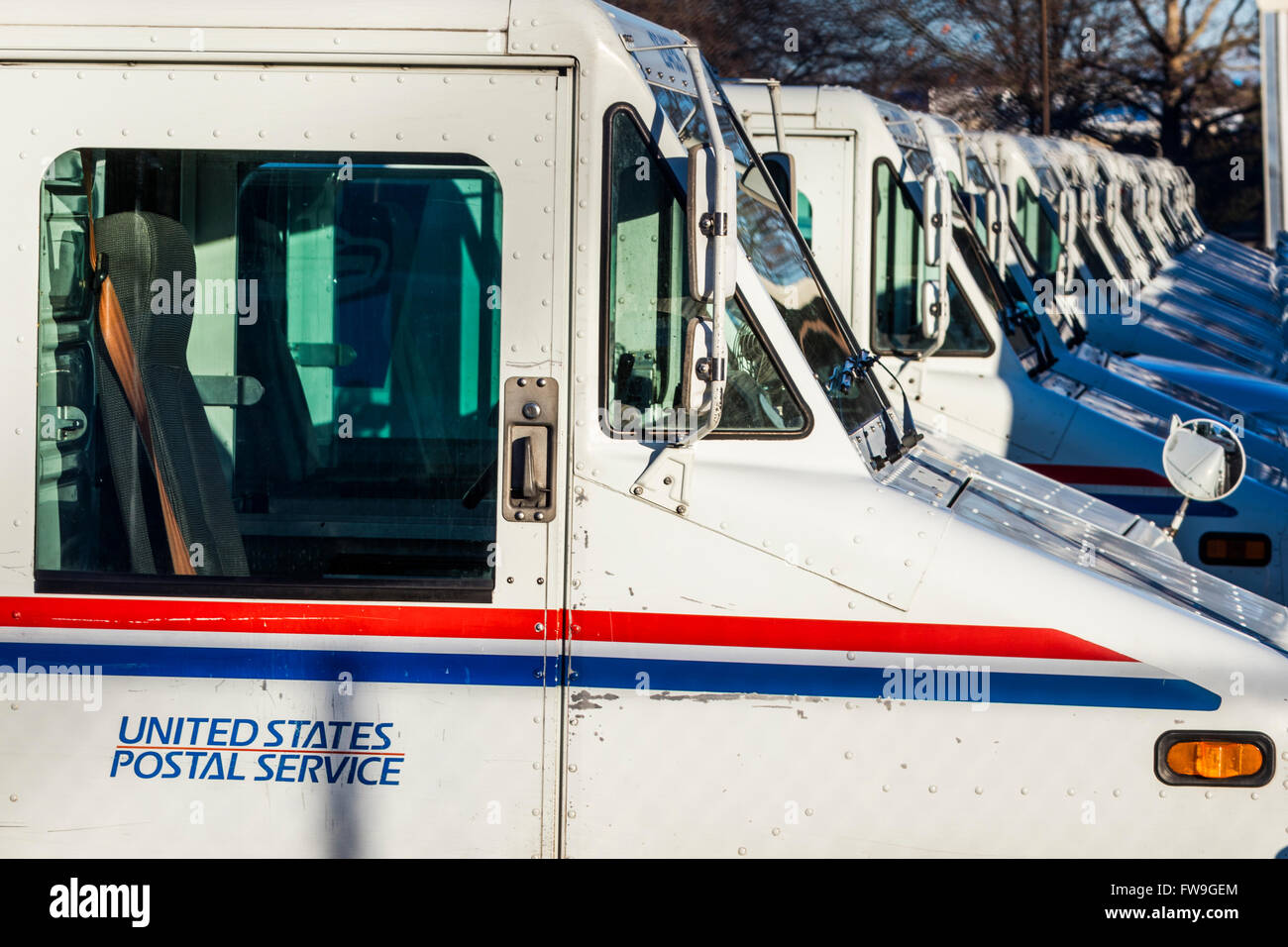 row of parked United States Postal Service vans - Stock Image