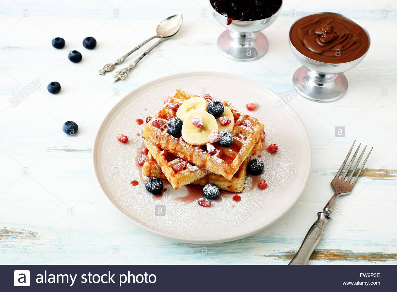 waffles with fresh berries and banana on kitchen table background - Stock Image