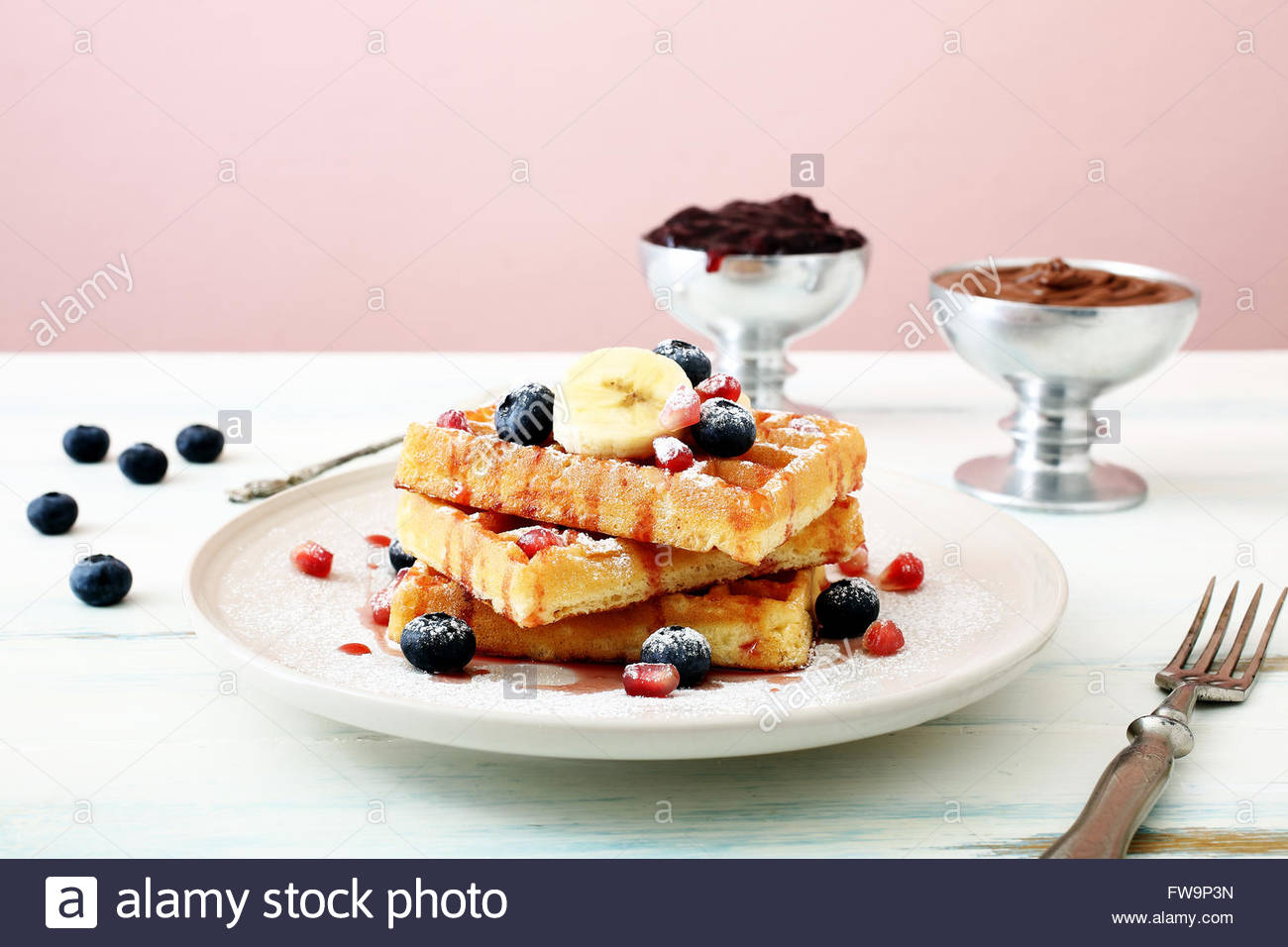 top view Belgian waffles with fresh berries and banana on kitchen table background - Stock Image