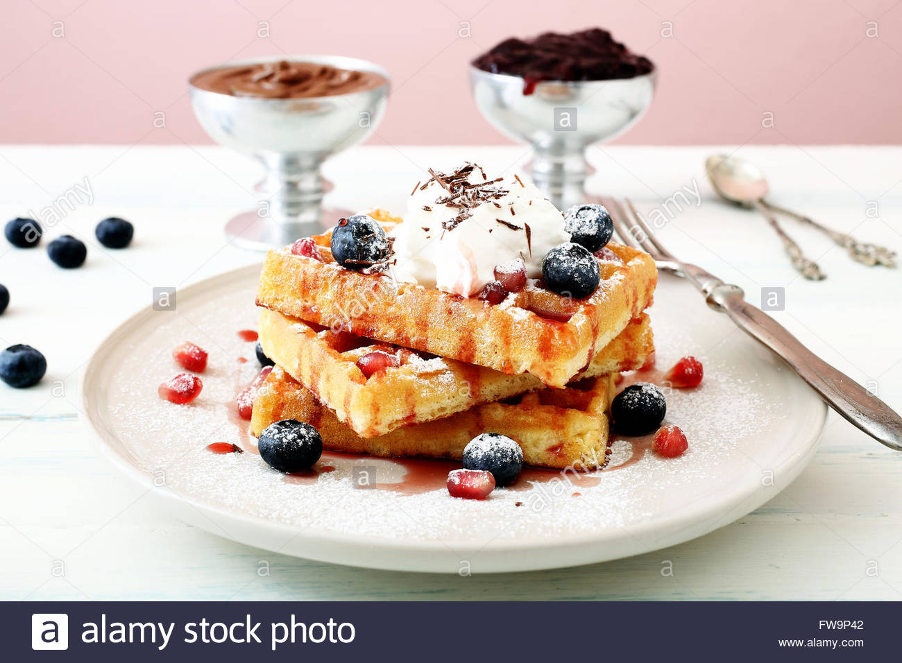 Belgian waffles with fresh berries on kitchen table background - Stock Image