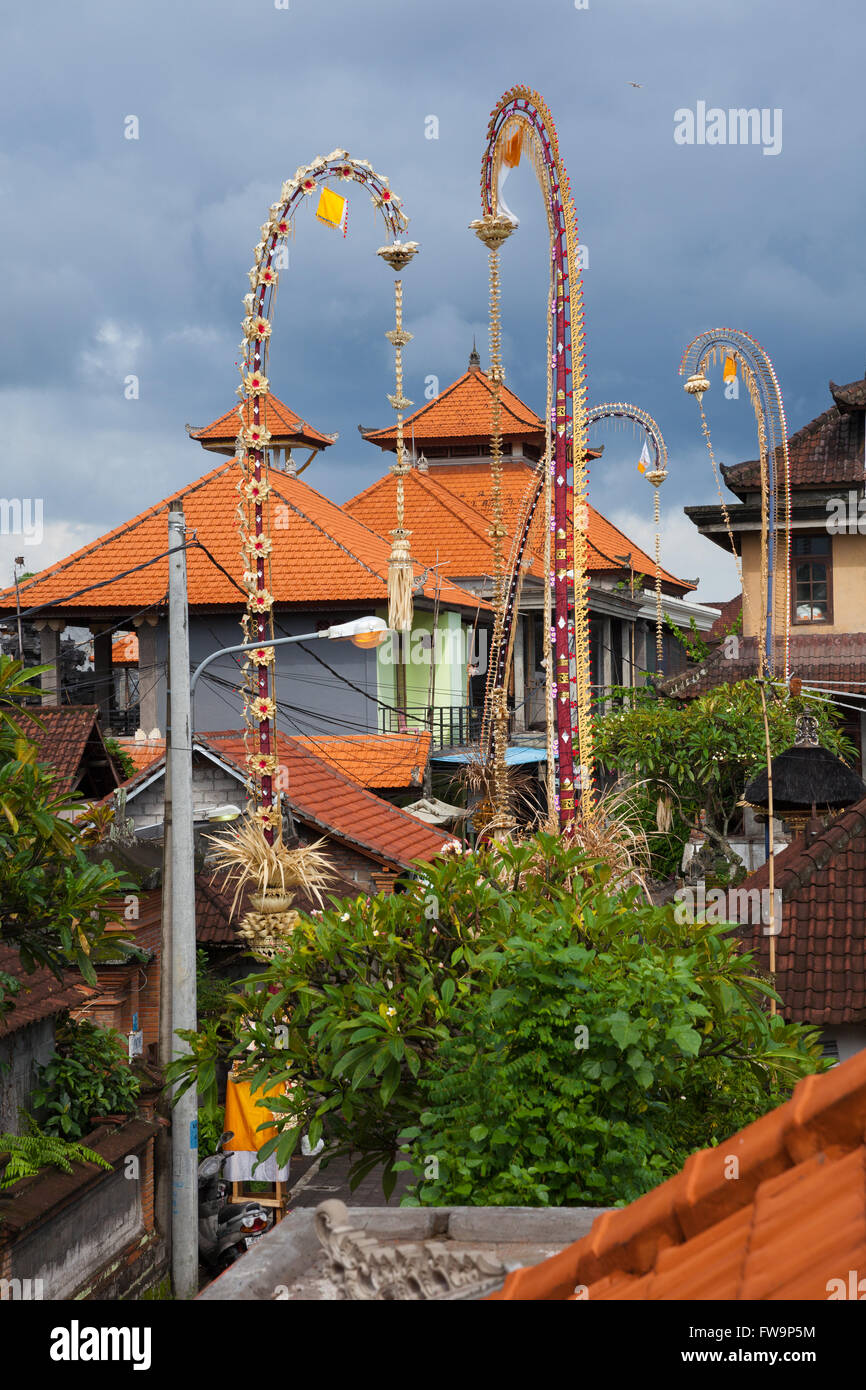 Traditional balinese roofs and ceremonial bamboo decorations on the street during celebrations of Nyepi, Day of - Stock Image