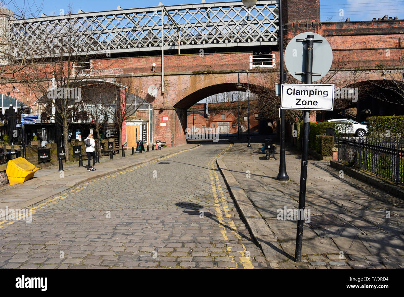 Signpost in Castlefields, Manchester, advising the area is a wheel clamping zone for unauthorised or illegal car - Stock Image