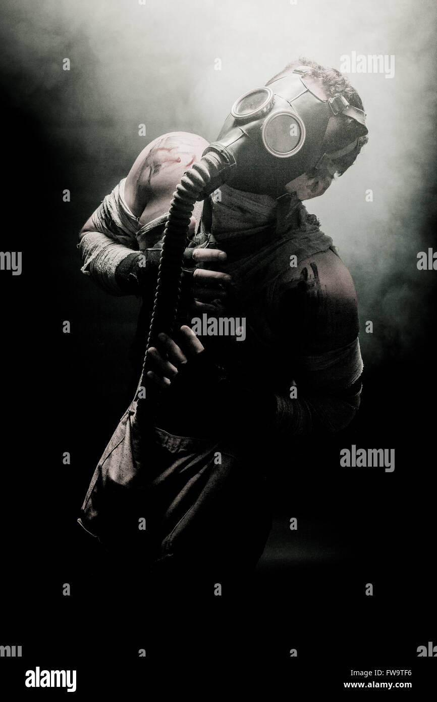 bandaged men in the gas mask on the black background surrounded by smoke and looking at the sky, survival soldier - Stock Image