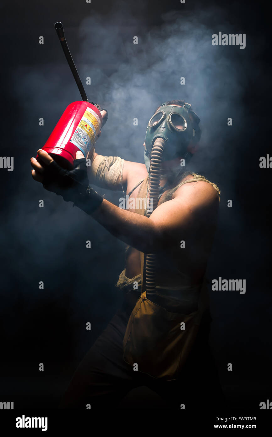 man in the gas mask with fire extinguisher, survival human after apocalypse. - Stock Image