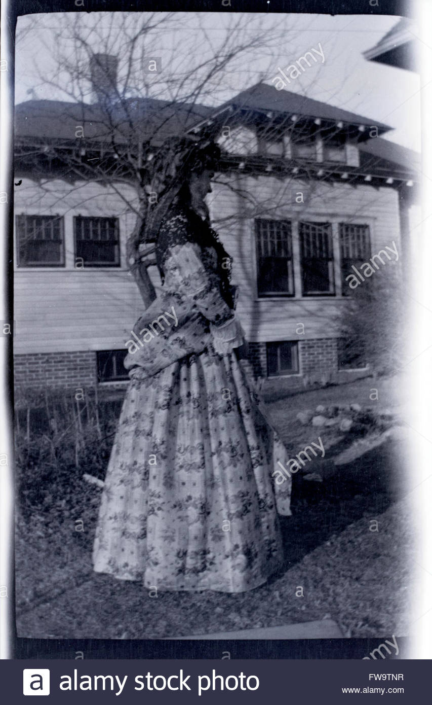 fashionable dressed young adult woman standing by house rural USA 1920s 1930s - Stock Image