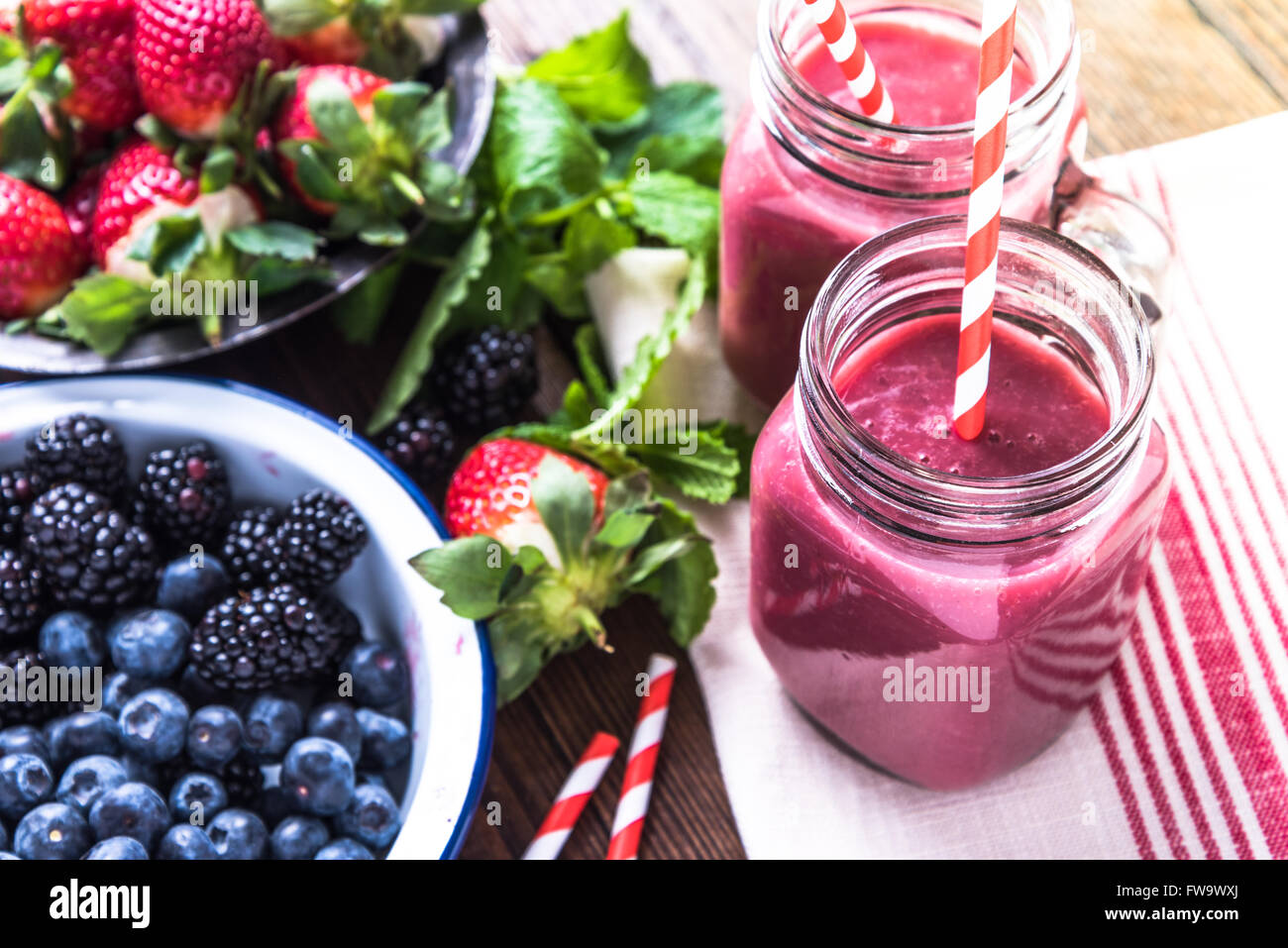 Well being and weight loss concept, berry smoothie.On wooden table with ingredients, from above. - Stock Image