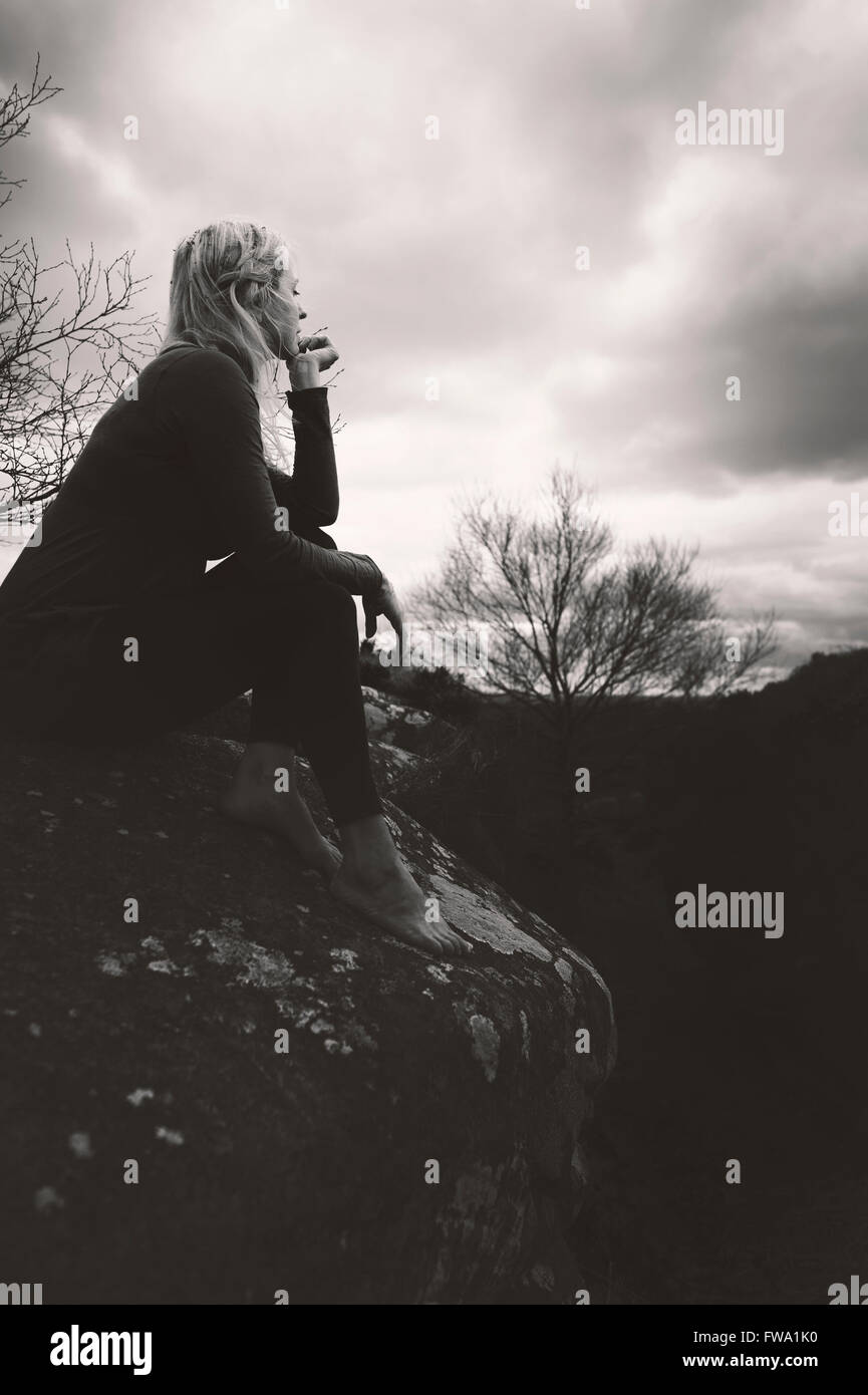 profile of the young woman sitting on the rock and thinking - Stock Image