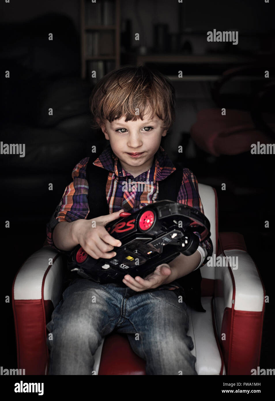 a boy sitting in armchair holding a car toy in dark room - Stock Image