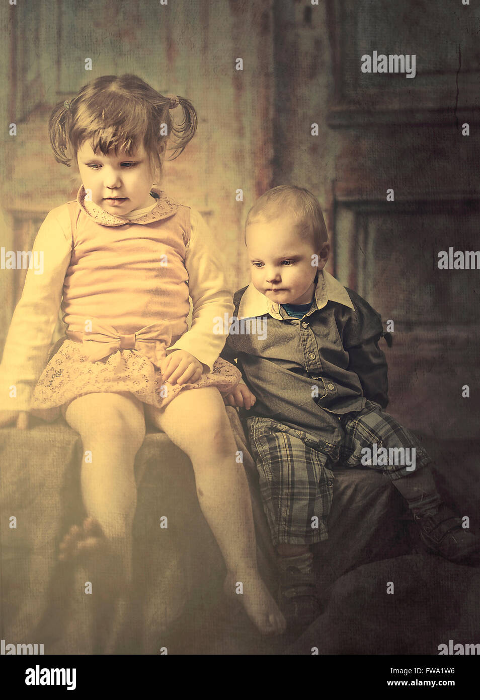 two small children siting next to each other looking down - Stock Image