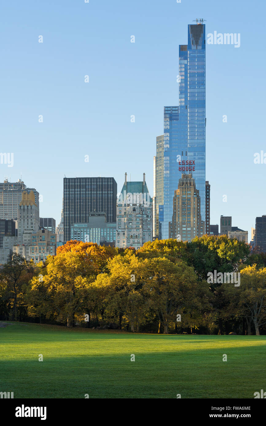 Autumn sunrise in Sheep Meadow, Central Park with view on Midtown Manhattan skyscrapers with One57 and Essex House. - Stock Image