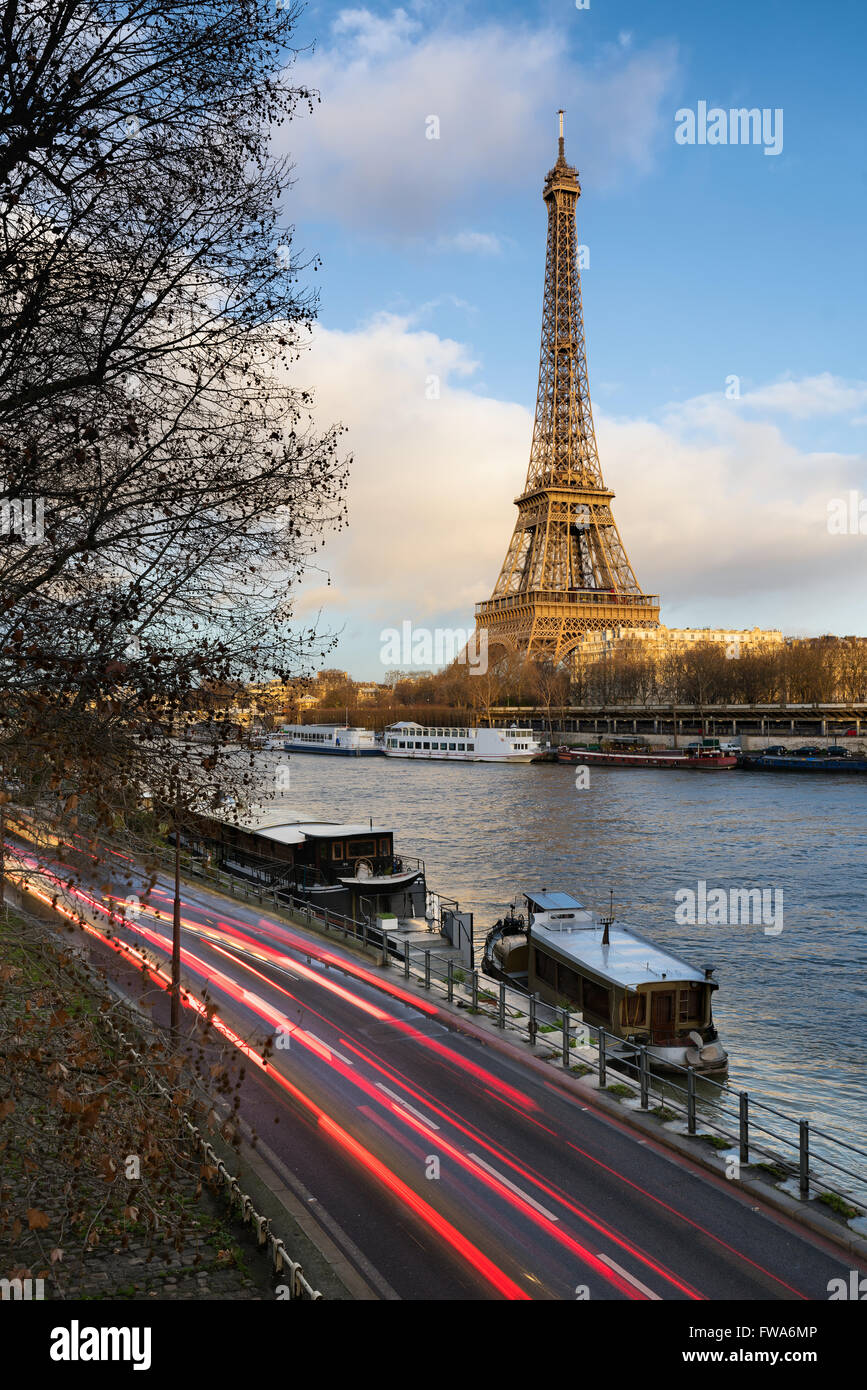 Before sunset at the Eiffel Tower along the Seine River in Paris with car light trails on Voie Georges Pompidou. Stock Photo