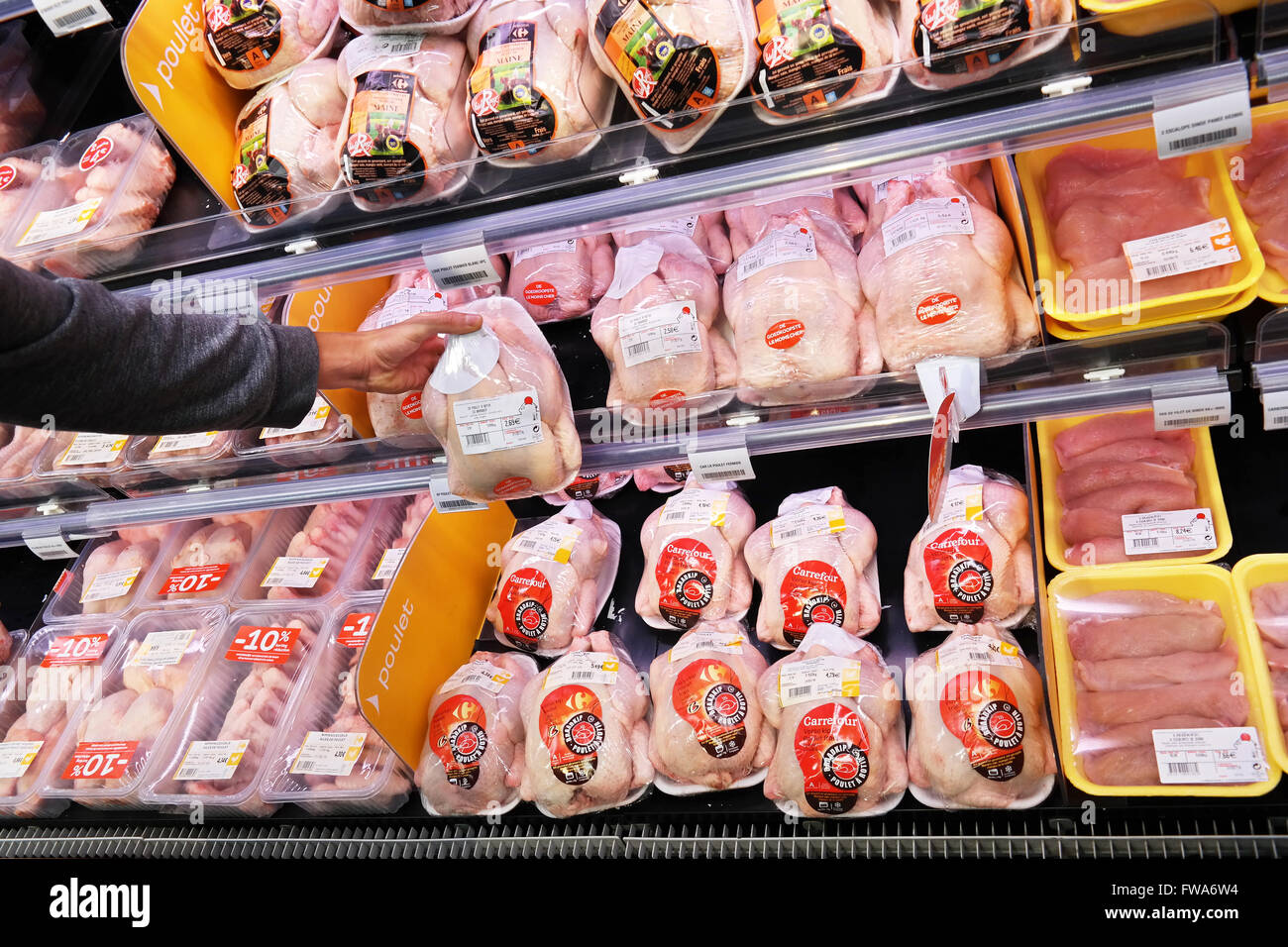 Customer selecting packaged chicken meat. - Stock Image