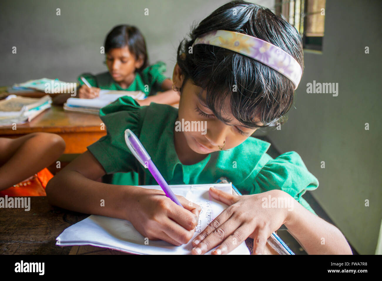 A little Girl writing NGO supported rural primary school classroom in SSS Center, Tangail, Dhaka © Jahangir - Stock Image