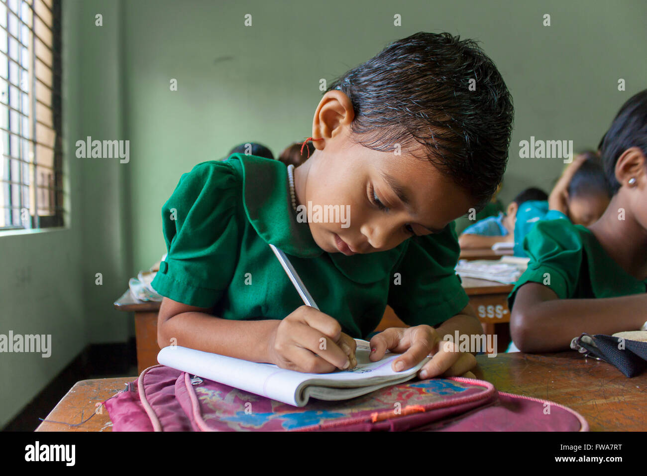 A little Girl writing rural primary school classroom in SSS (Society for Social Service) Center, Tangail, Dhaka - Stock Image