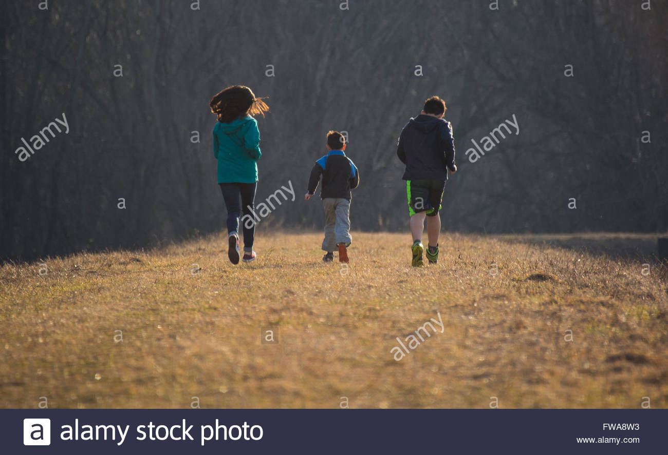 Three kids running in sync - Stock Image