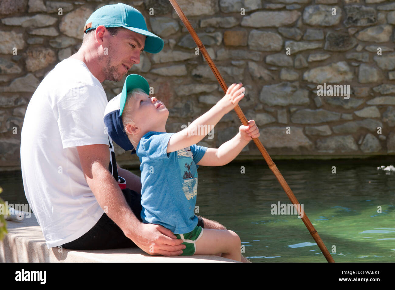 Father and son sitting at the edge of a pool dangling their feet in the water playing with a fishing net - Stock Image