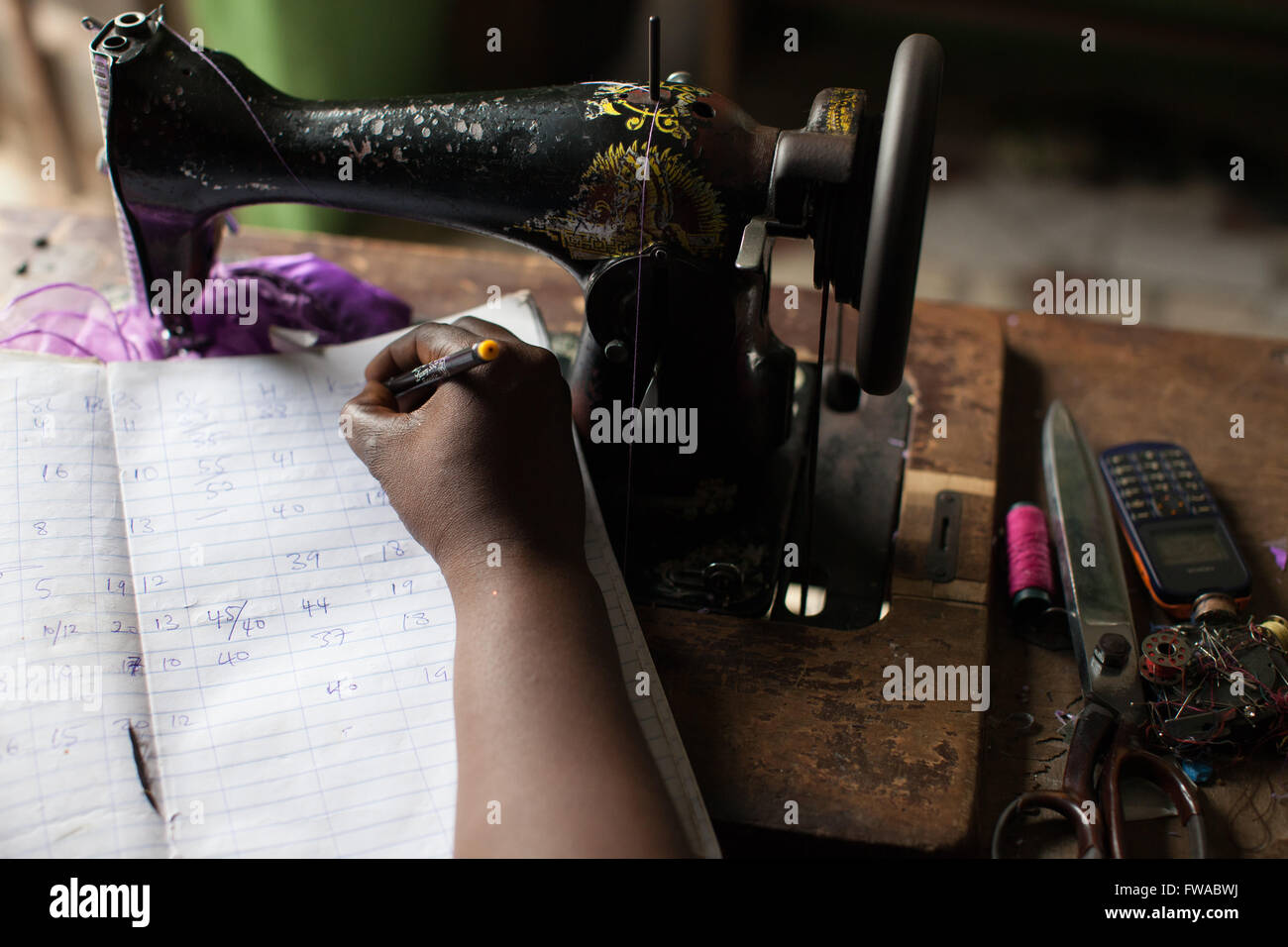 A female entrepreneur doing her bookkeeping for her dressmaking business Nigeria, Africa - Stock Image