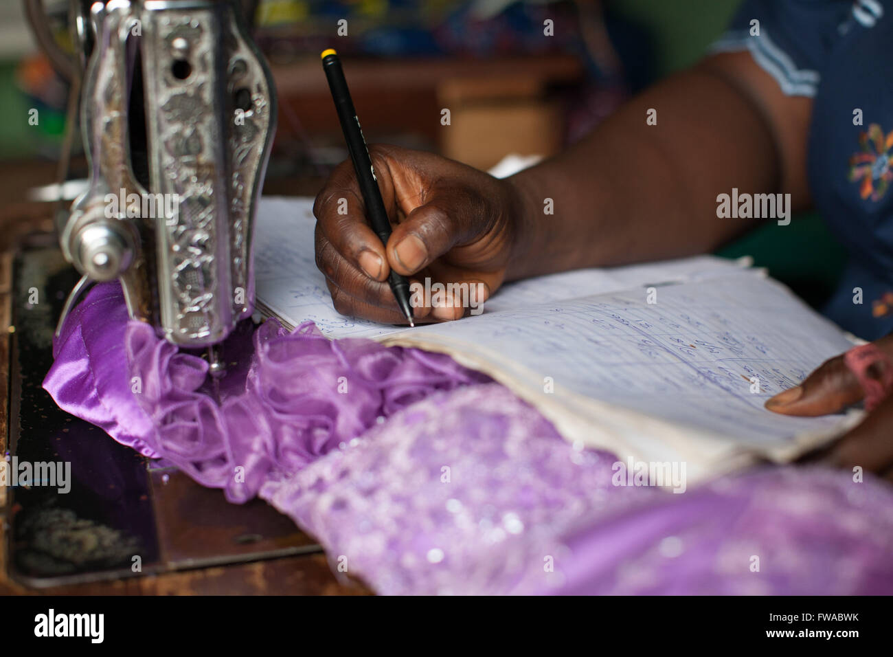 A female dressmaker doing some book keeping, Nigeria, Africa - Stock Image