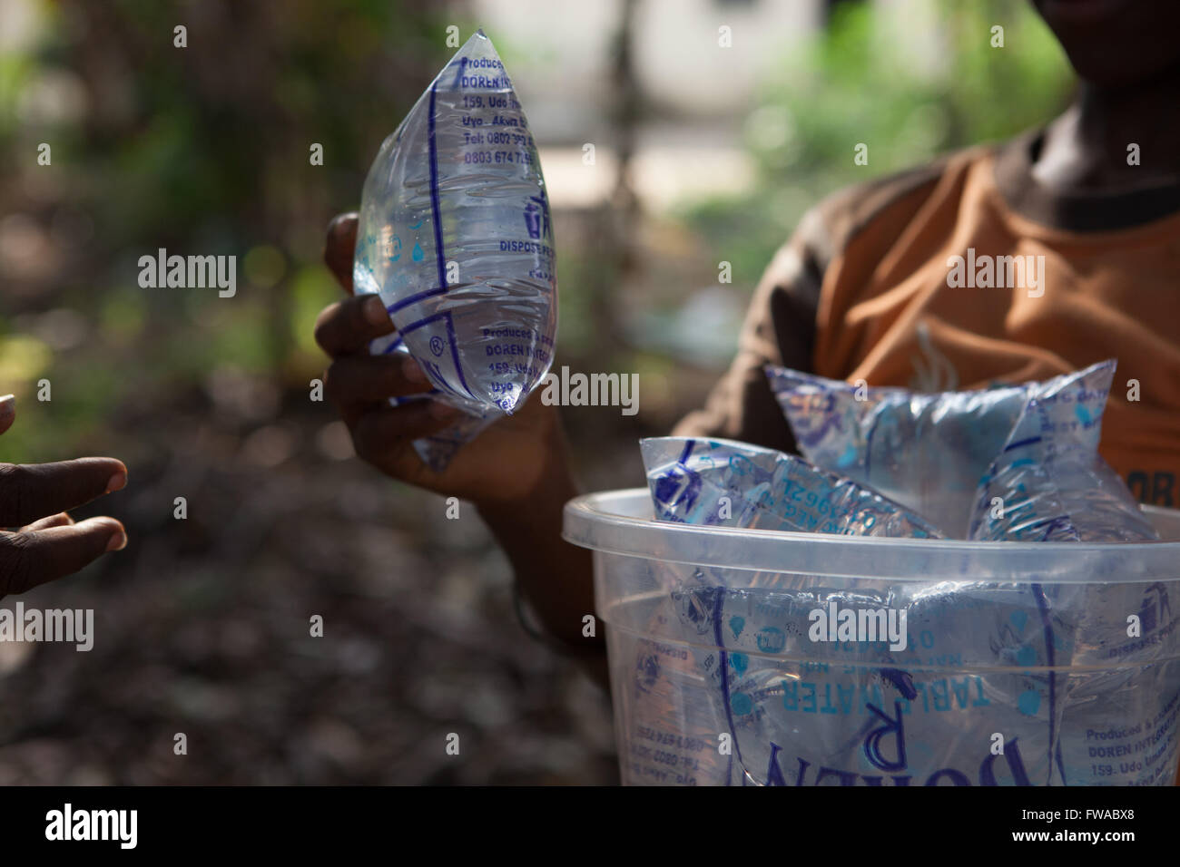 A boy selling sachets of purified water on the streets of Nigeria, Africa - Stock Image