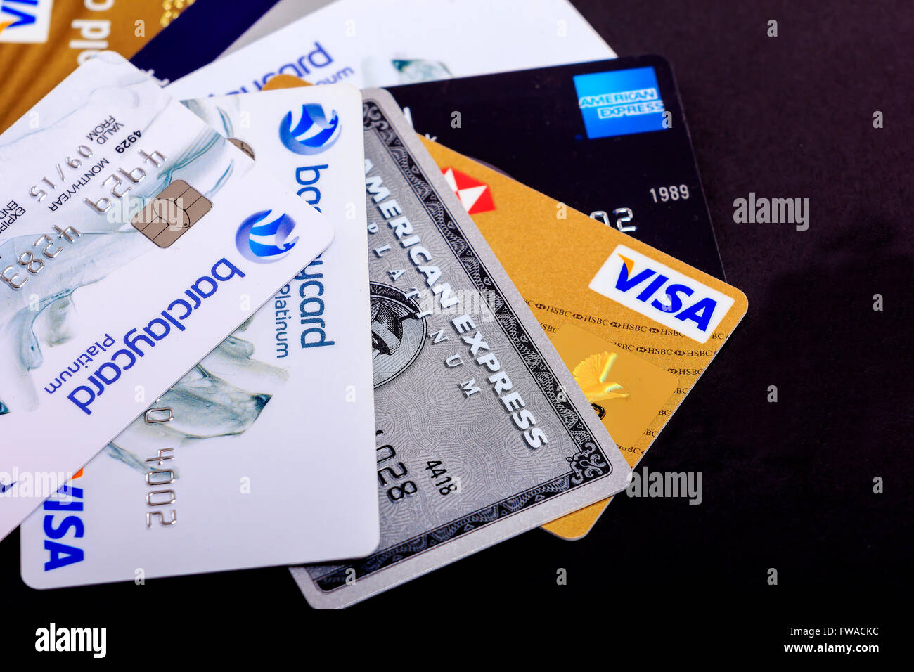 Selection of credit and charge cards spread on black background. - Stock Image