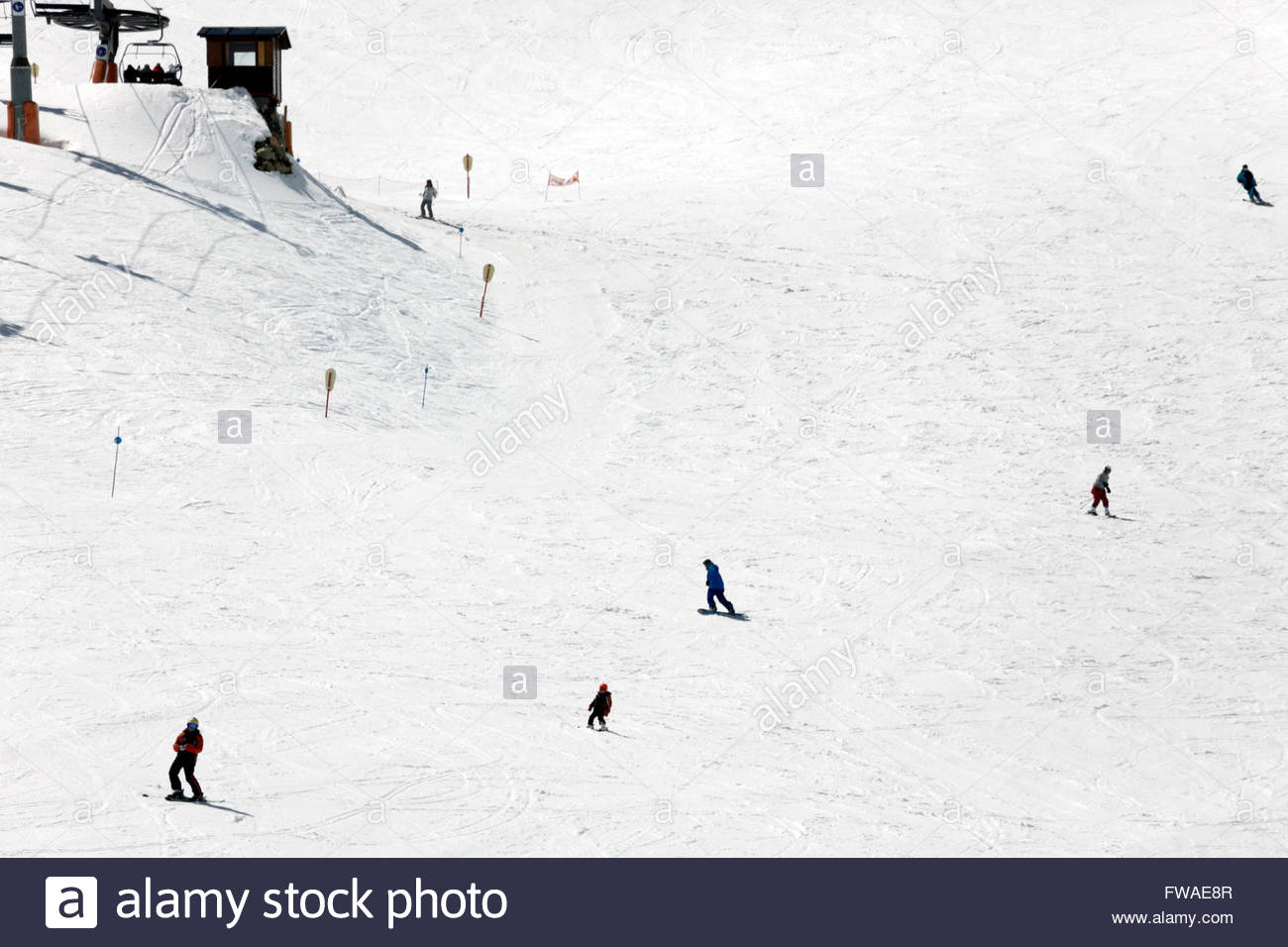 people on a large slope skiing down hill - Stock Image