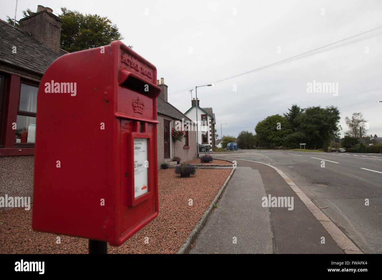 A small red postbox in a main road in the village of Corsock in Dumfrieshire, Scotland - Stock Image