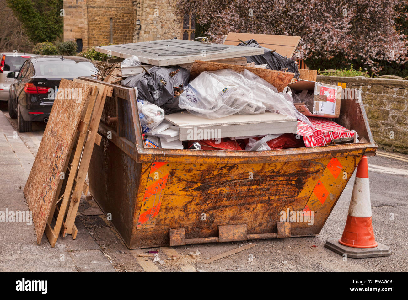 Builder's skip on the roadside, filled with rubble. - Stock Image