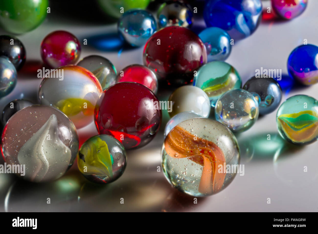 Closeup view of translucent marbles on a shiny surface - Stock Image
