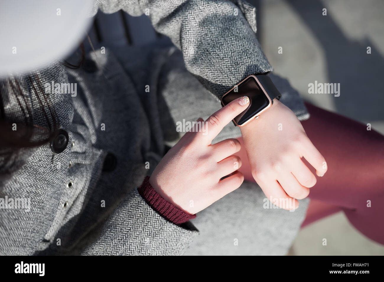 Woman in grey coat and marsala tights using her trendy smart wrist watch. This person is always connected to social - Stock Image