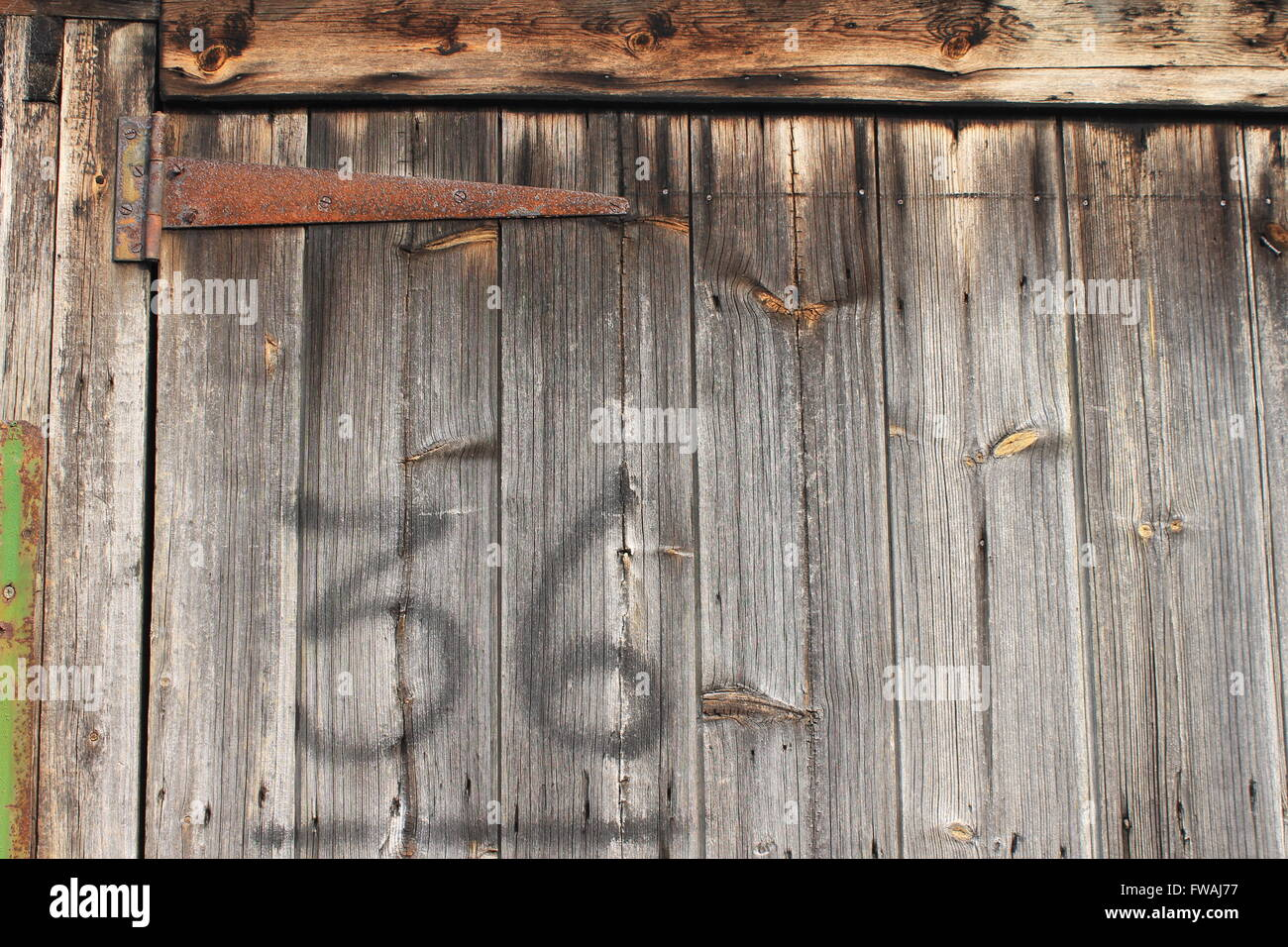 36; number 36 sprayed on to old wooden fronted garage door with a large rusty hinge - Stock Image