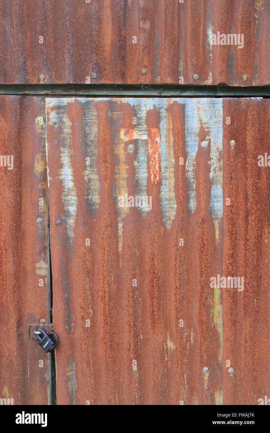 Rusty, corrugated sheet metal shed door and padlock Stock Photo