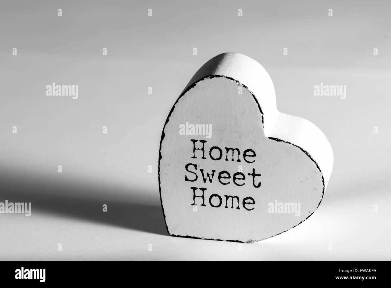 heart shaped object with the words home sweet home painted on it - Stock Image