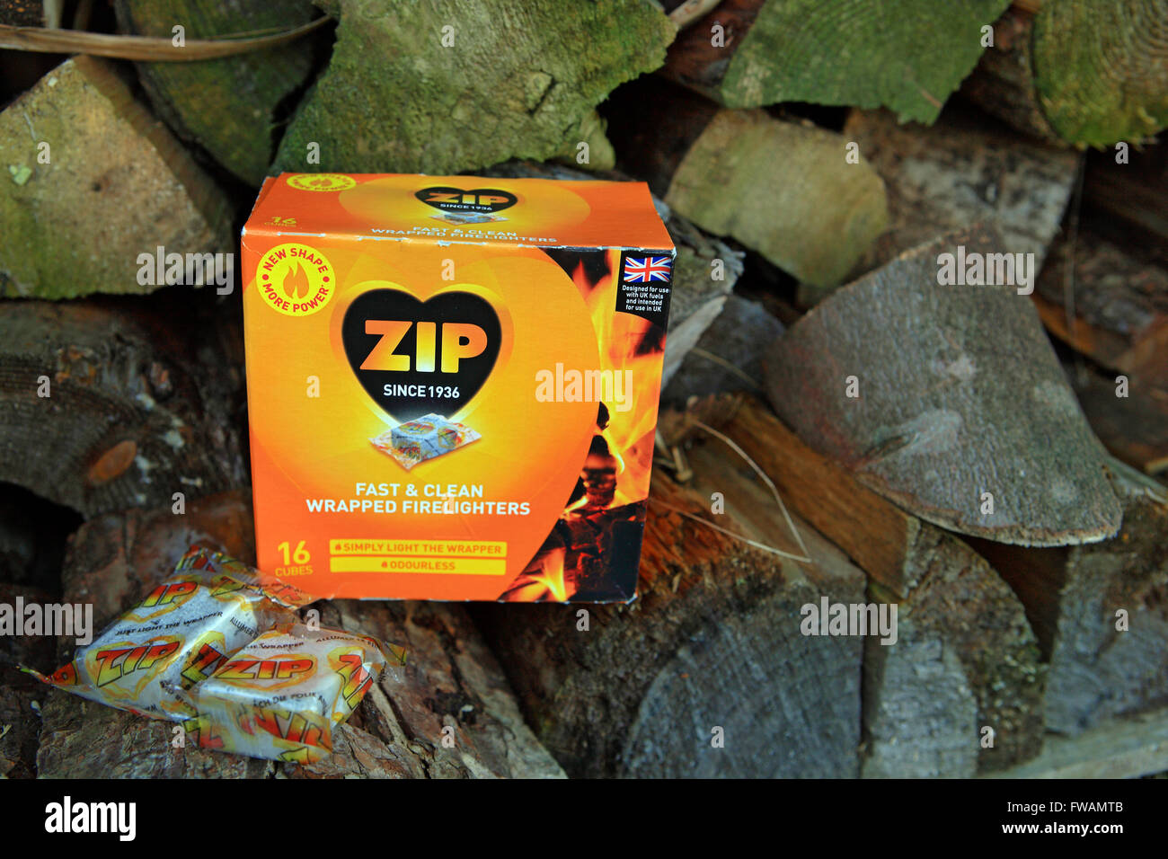 Zip firelighters sitting on file of cut fire wood - Stock Image