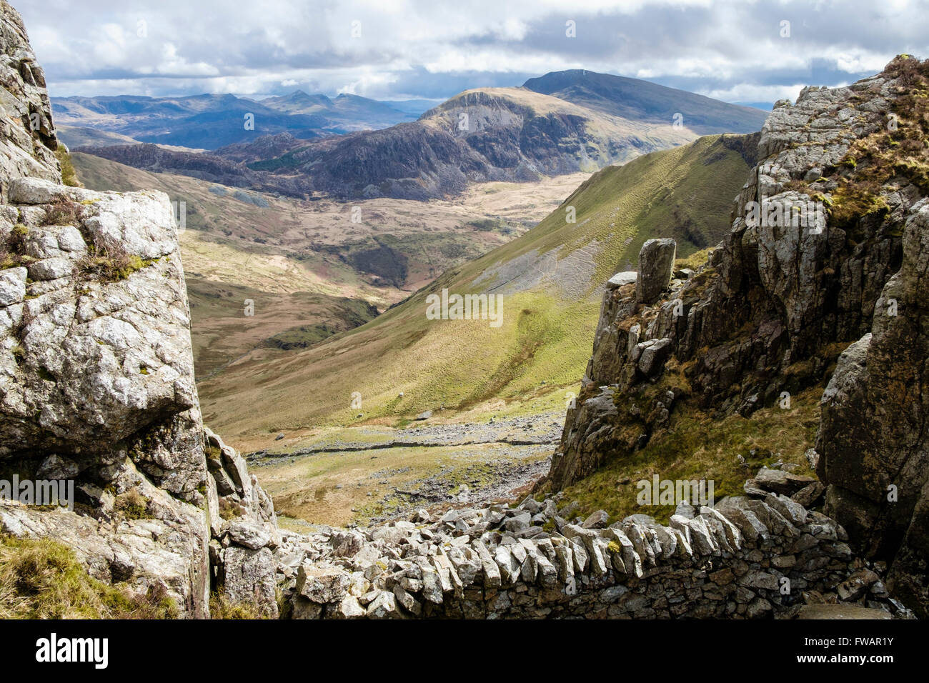 View SE to distant Moel Hebog across Cwm Pennant from Craig Cwm Silyn on Nantlle Ridge in Snowdonia National Park Stock Photo