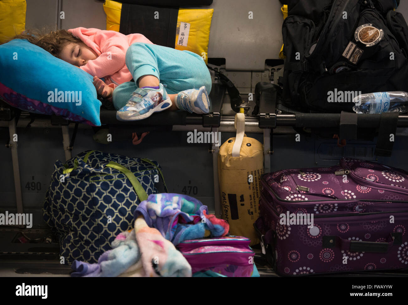 Amelia McNab, 2, sleeps aboard a C-17 Globemaster transport aircraft after being evacuated from Incirlik Air Base - Stock Image