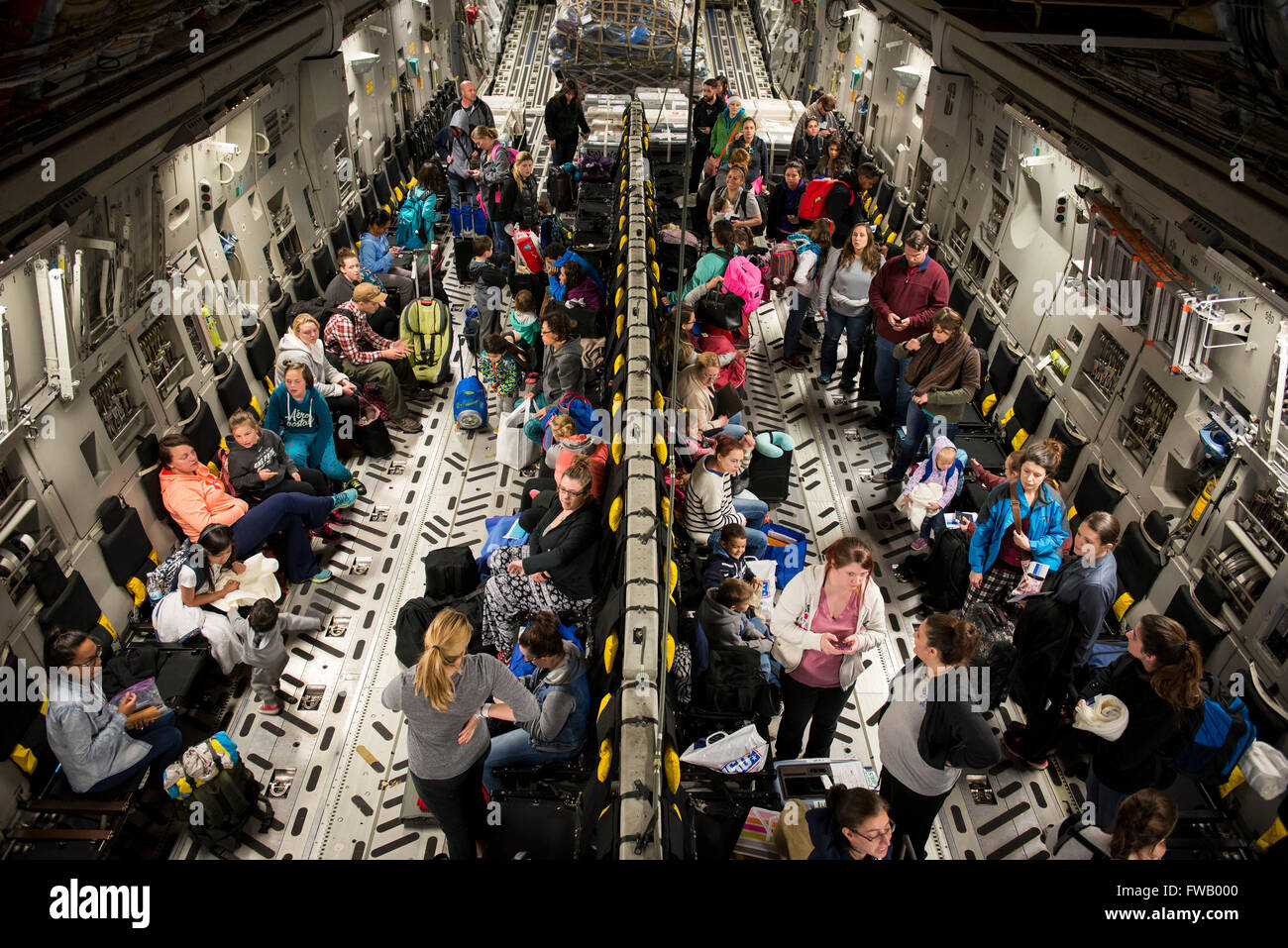 U.S. military family members wait aboard a C-17 Globemaster transport aircraft after being evacuated from Incirlik - Stock Image