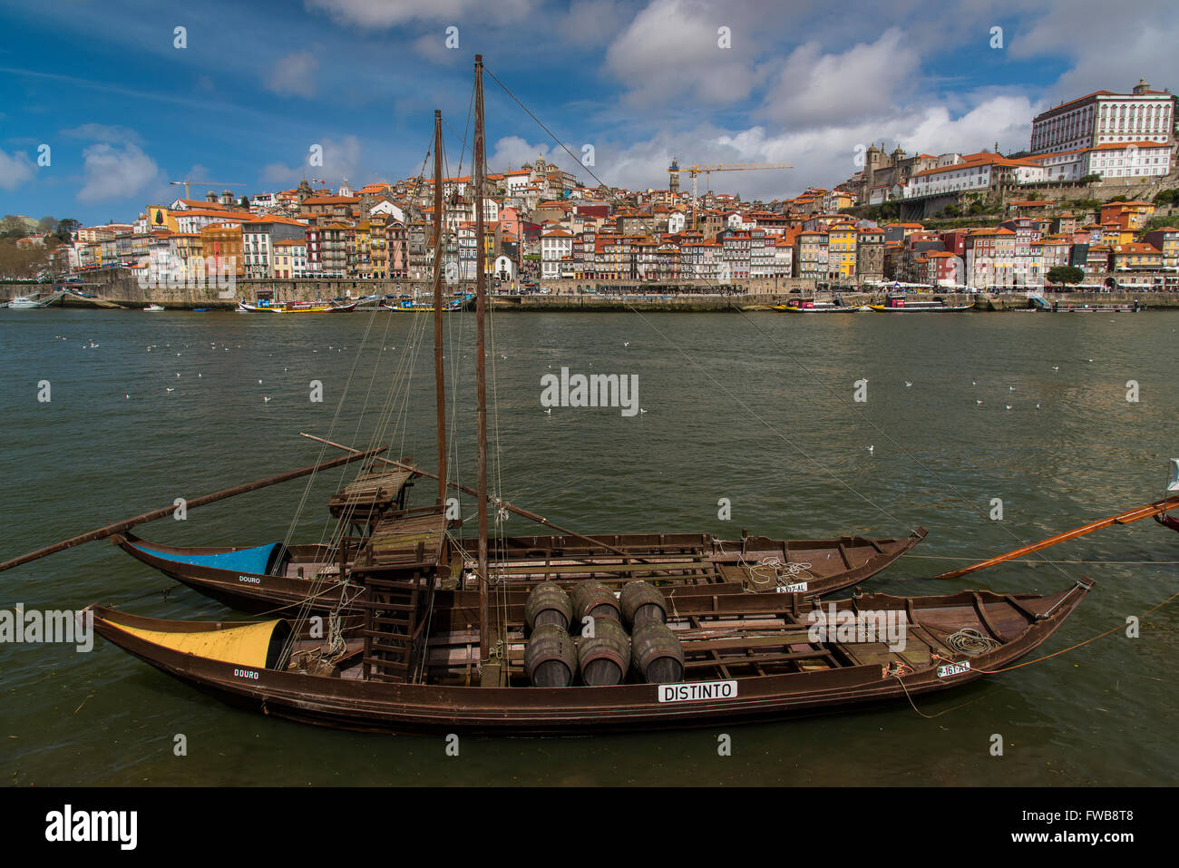 Traditional Rabelo boat designed to carry wine down Douro river with city skyline behind, Porto, Portugal - Stock Image