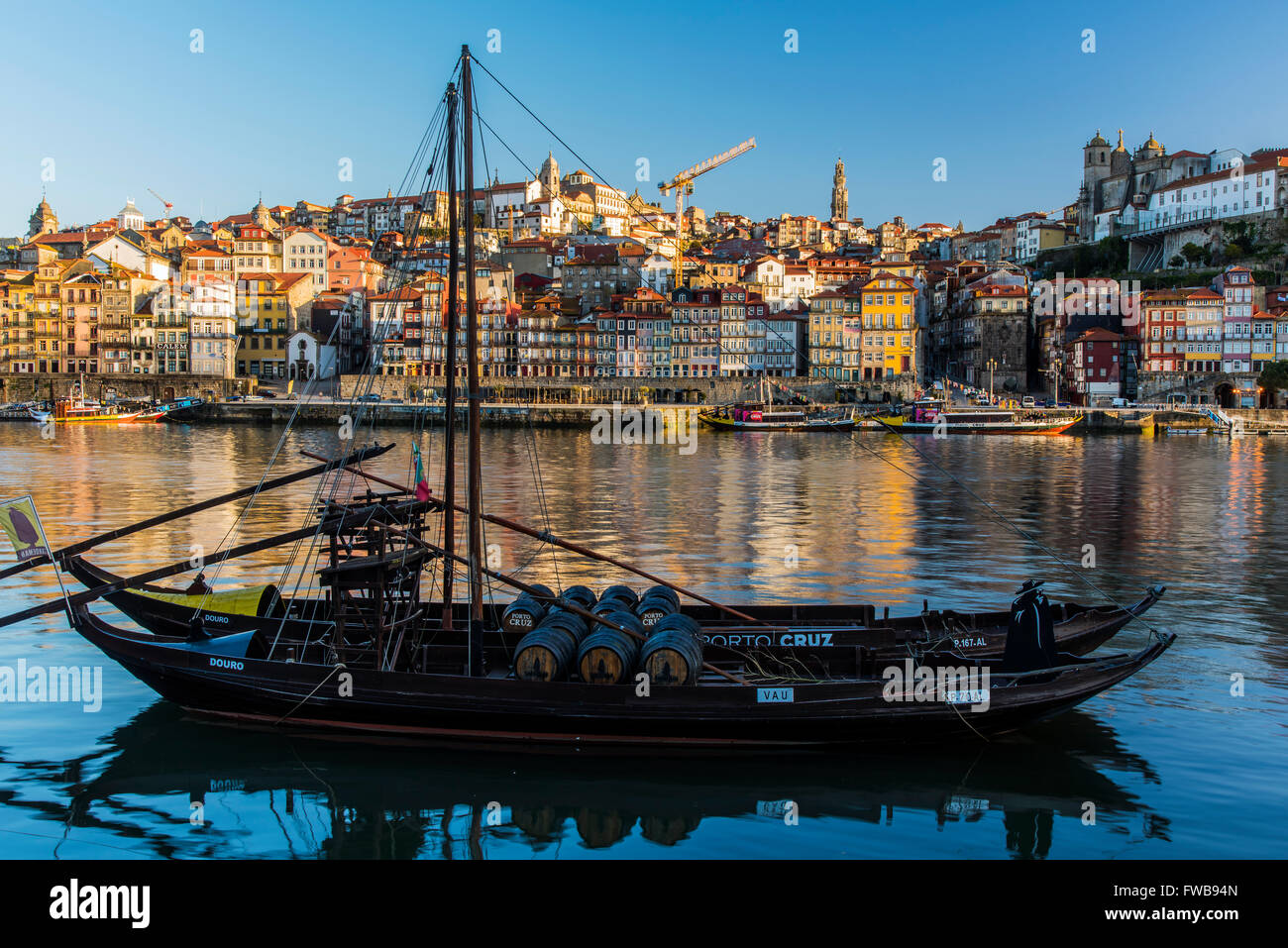 Traditional Rabelo boat designed to carry wine down Douro river with city skyline behind, Porto, Portugal Stock Photo