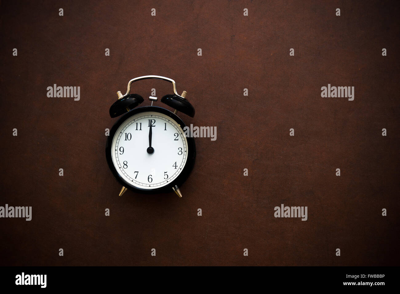 Vintage alarm clock reminder symbol on noon midnight hour on wooden background - Stock Image