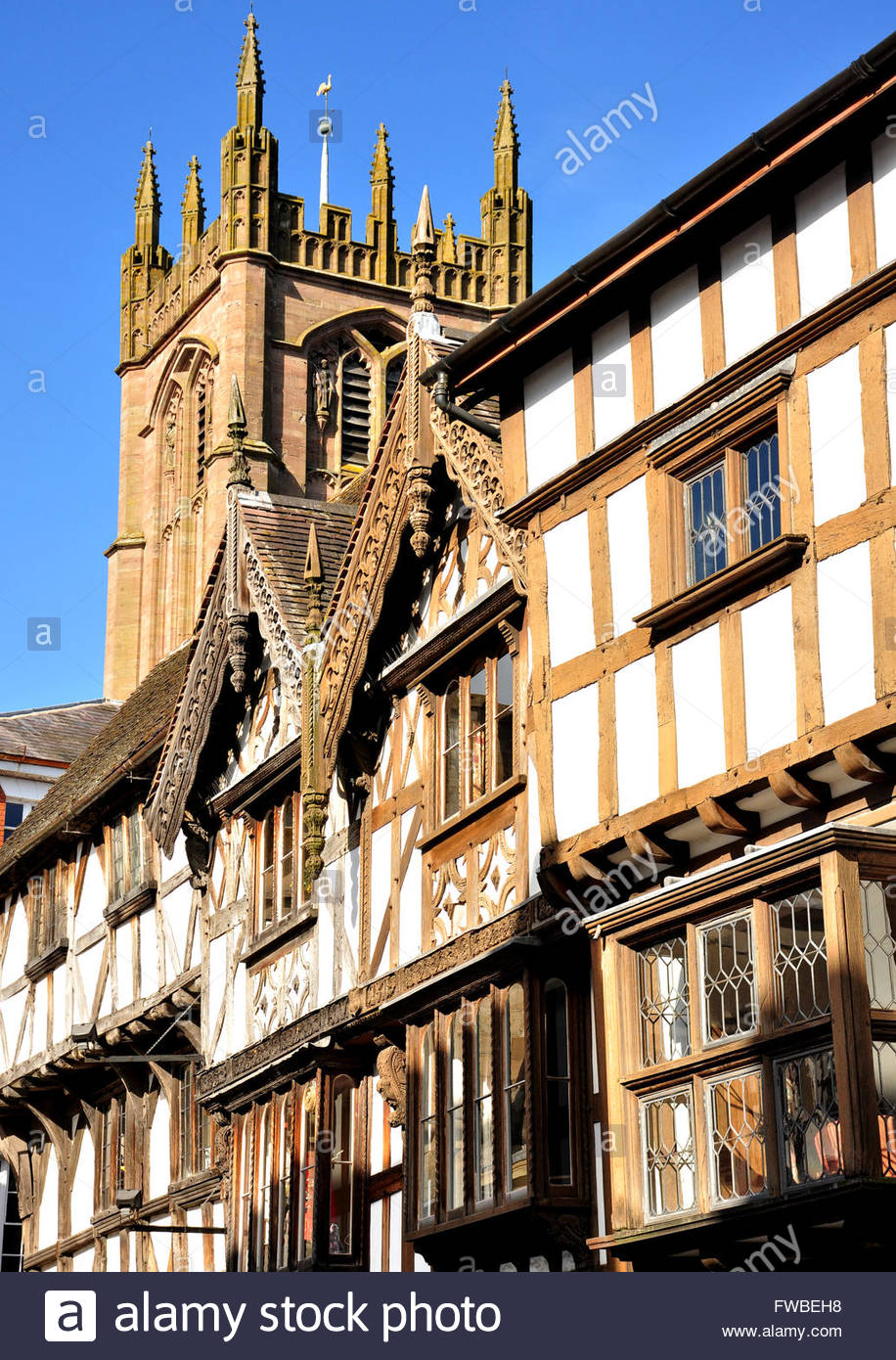 St Laurence's parish church in Ludlow, UK towers over some of the historic half timbered buildings on Broad - Stock Image