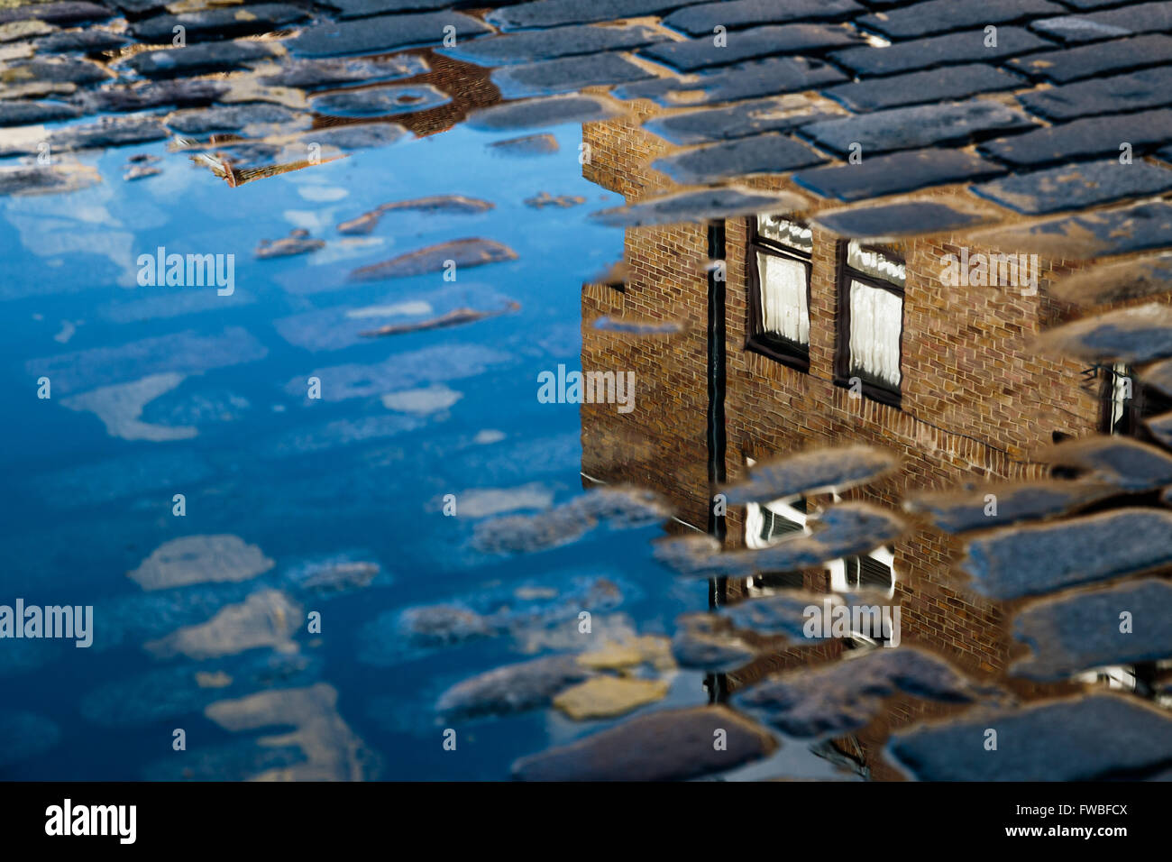 Cobblestone with reflection of house in puddle after rain - Stock Image