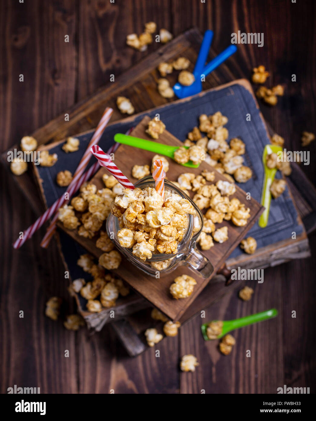 Sweet popcorn with bright colored straws and spoons shot  from above - Stock Image